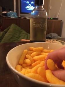 Bild med ostbågar framför teve.